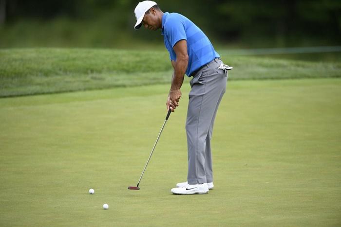 Tiger Woods đứng hơi cúi mình về trước khi thực hiện kỹ thuật gạt bóng